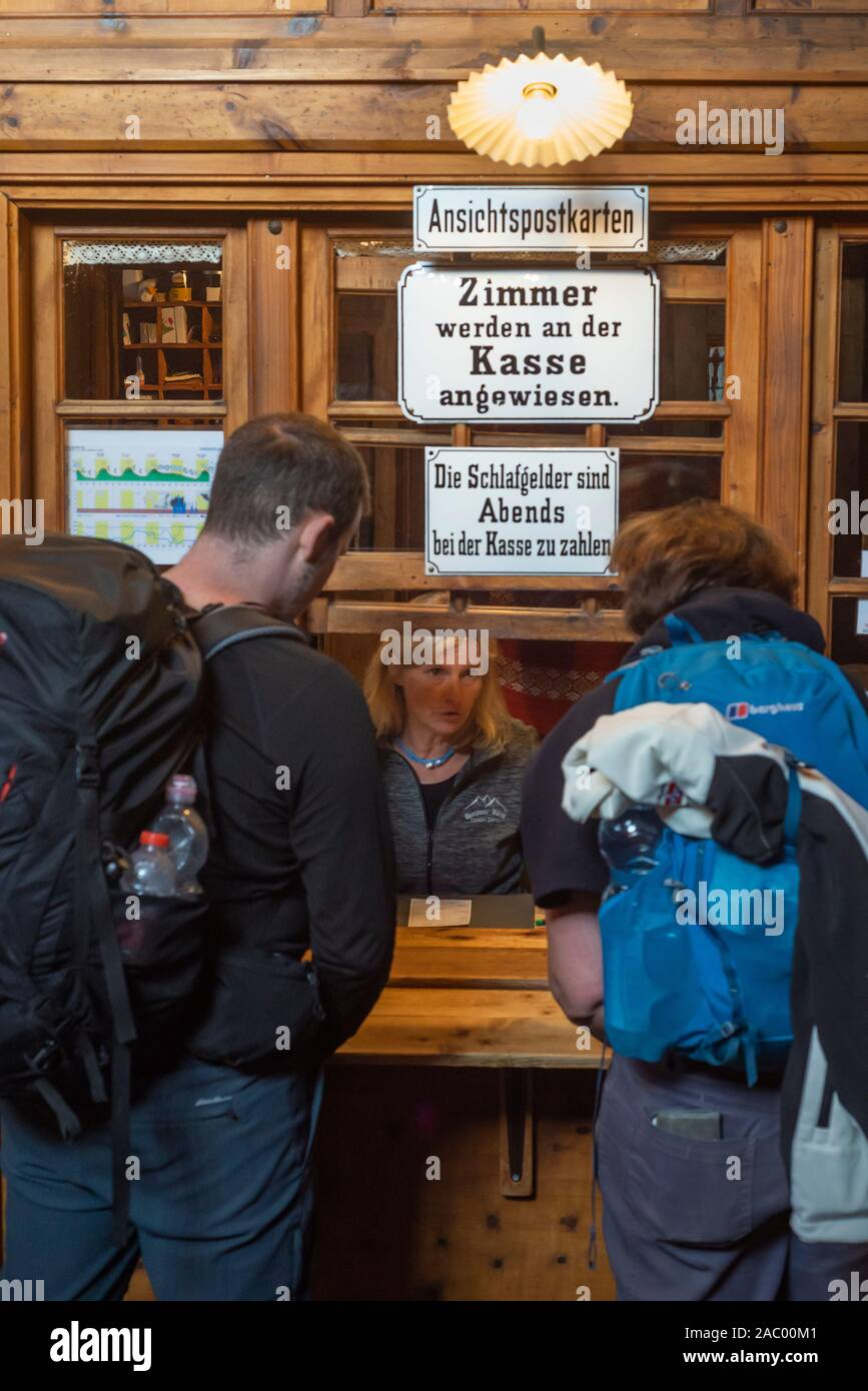 Mountain hikers talking to a woman at the reception desk of the Berliner Hütte, Zillertal, Tyrol, Austria Stock Photo