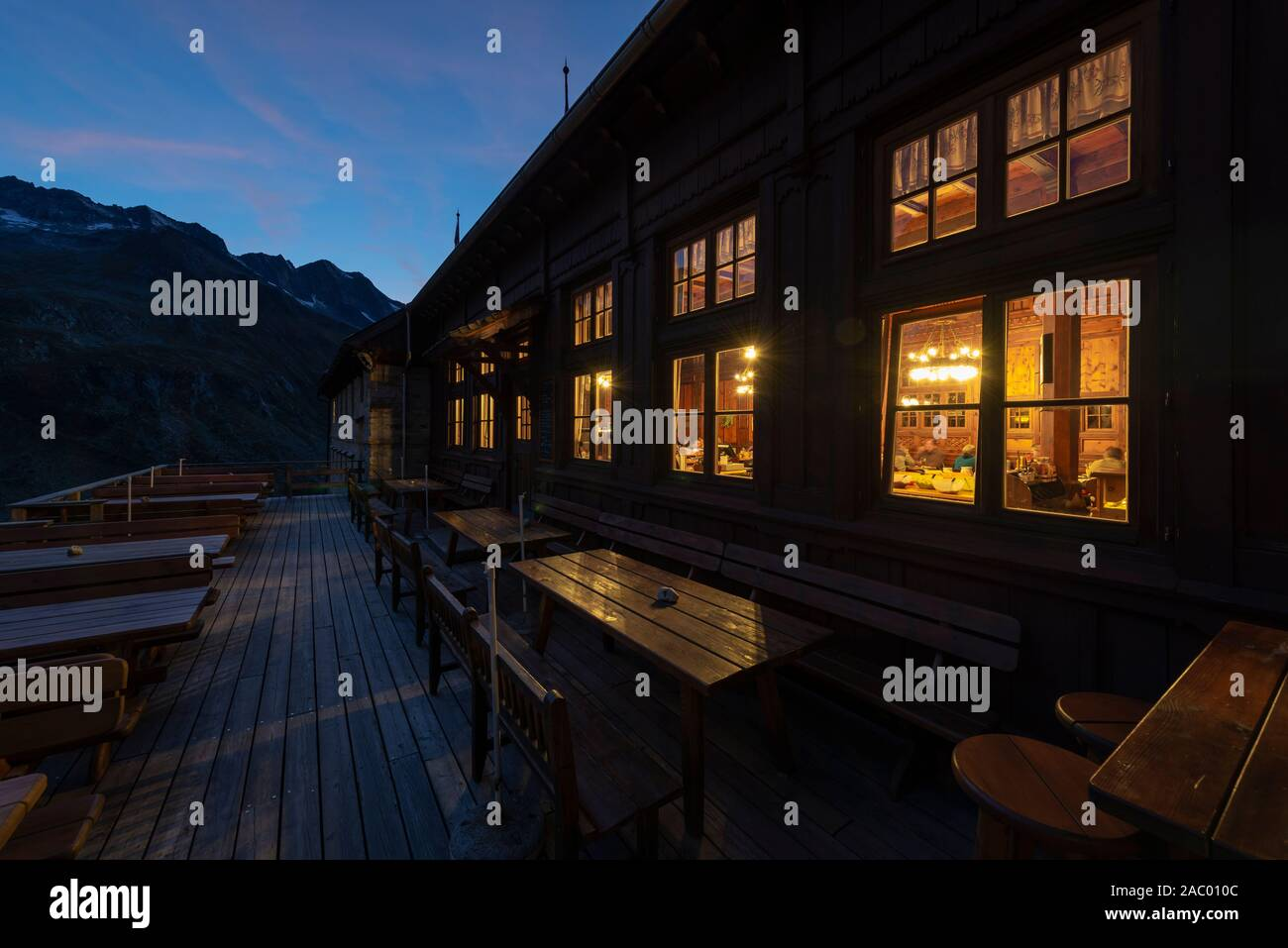 View of the illuminated dining room of the Berliner Hut during sunset , Zillertal, Tyrol, Austria Stock Photo