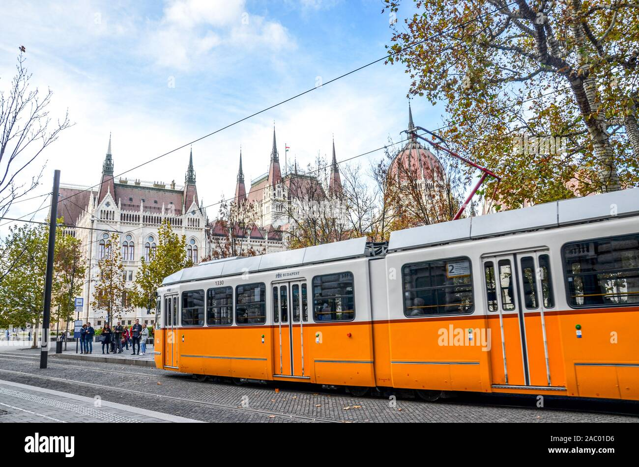 Budapest, Hungary - Nov 6, 2019: Public yellow tram riding in front of the Hungarian Parliament building. Hungarian capital city public transport. City transportation. Tourist attraction. Stock Photo