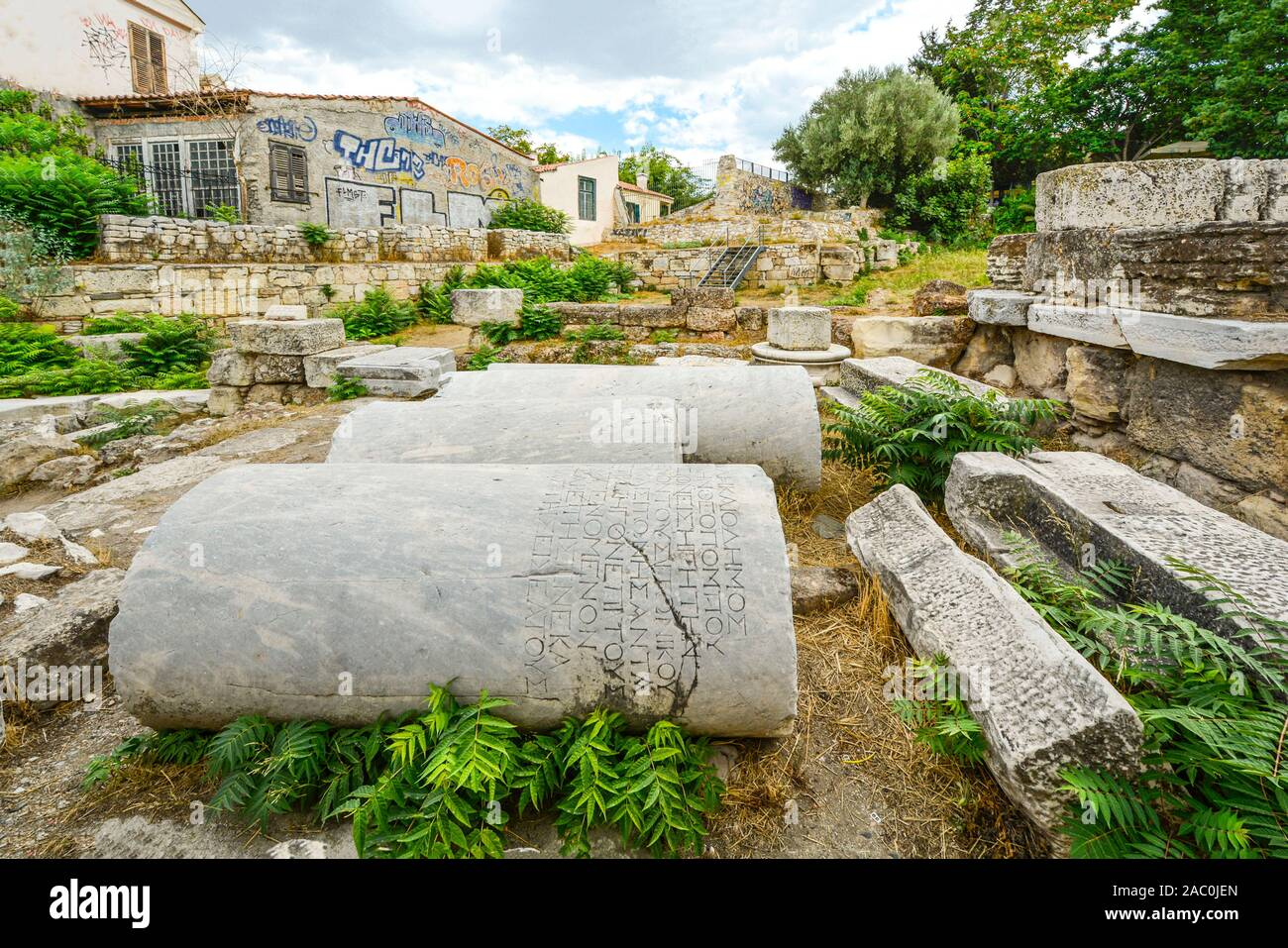 Ancient columns with inscriptions lay beside a new building covered with Graffiti in Athens, Greece. Stock Photo