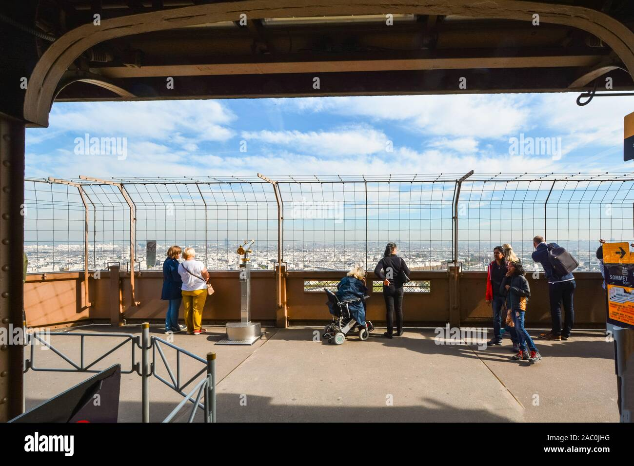 Tourists including a woman in a wheelchair enjoy the view from the first platform of the Eiffel Tower on a sunny day in Paris France Stock Photo