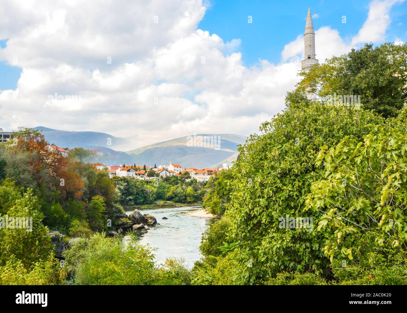 The river Neretva flows by the ancient wall surrounding the old town section of Mostar, Bosnia Stock Photo