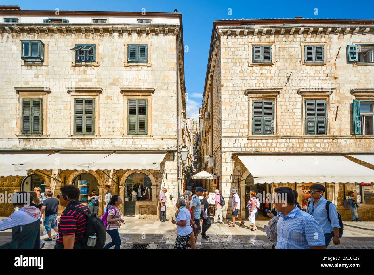 Tourists walk the main street or Stradun as they pass a narrow staircase up to the wall in the walled city of Dubrovnik Croatia. Stock Photo
