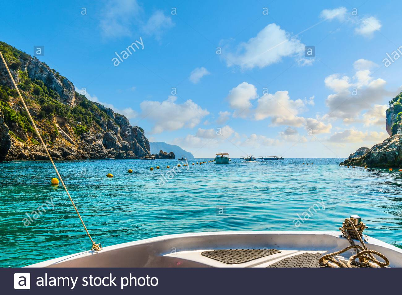A small boat heads towards other boats and out of the Palaiokastritsa  bay towards the Aegean Sea on the Island of Corfu Greece. Stock Photo
