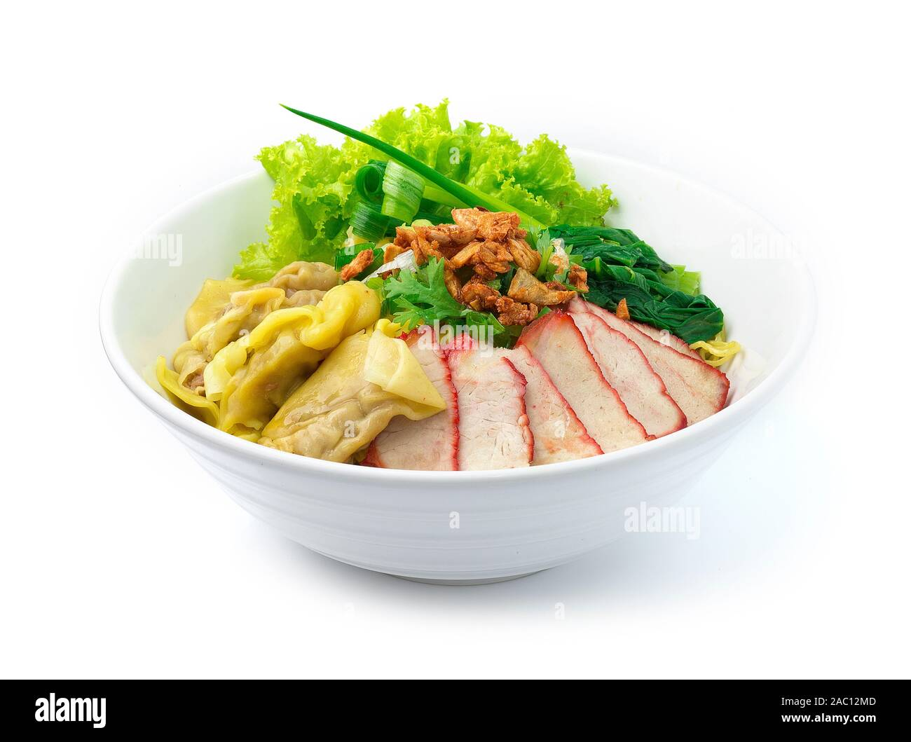 Egg Noodles with Red roast Pork and Wonton Dumplings ontop Crispy Garlic and Spring Onions in Bowl. Asian Food fusion style side view Stock Photo