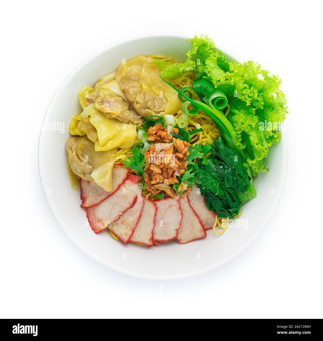 Egg Noodles with Red roast Pork and Wonton Dumplings ontop Crispy Garlic and Spring Onions in Bowl. Asian Food fusion style top view Stock Photo