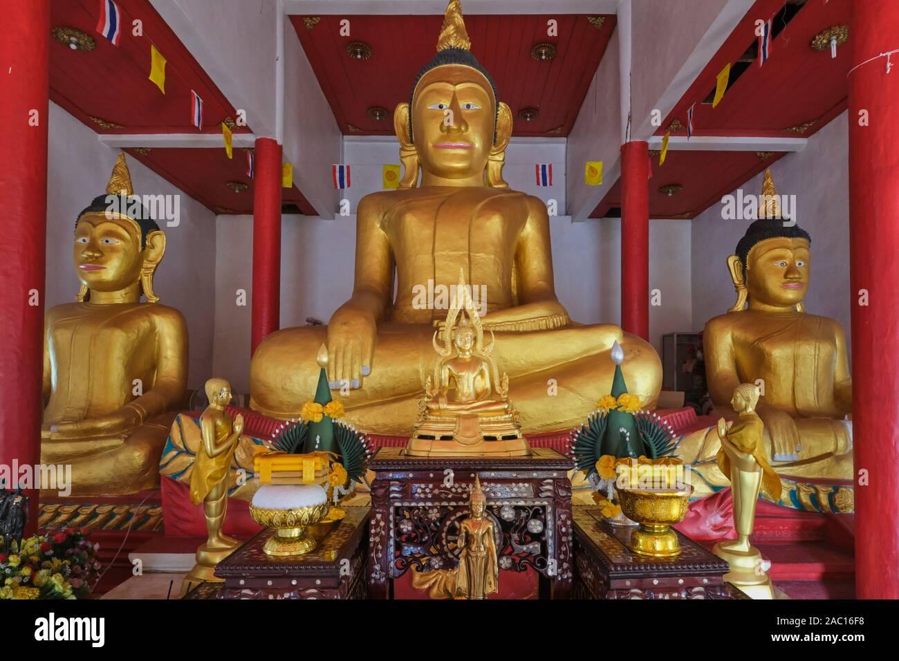 The ancient three tin Buddha statues in the old Bot or Ubosot (ordination hall) of  Wat Phra Nang Sang, Thalang, Phuket, Thailand Stock Photo