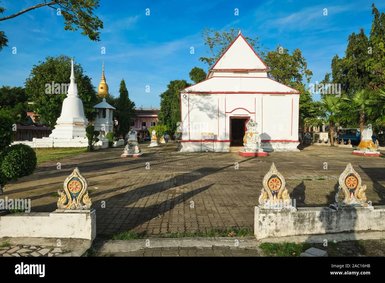 The old Bot or Ubosot (ordination hall) of Wat Phra Nang Sang, Thalang, Phuket, Thailand, a chedi (stupa) on the left, sema (marker) stones in front Stock Photo
