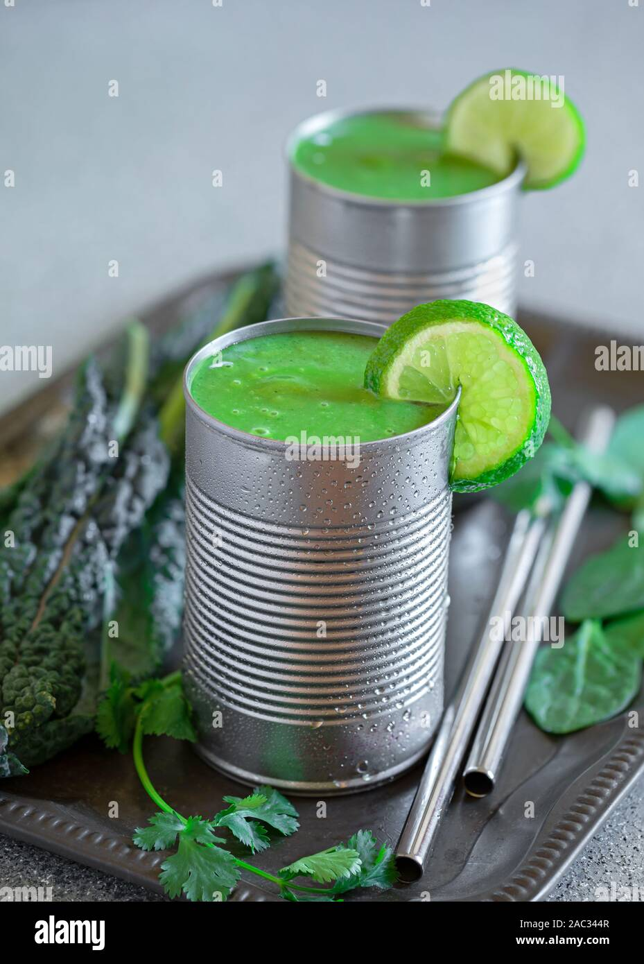 Healthy kale and spinach smoothies served in repurposed metal cans with stainless steel drinking straws Stock Photo