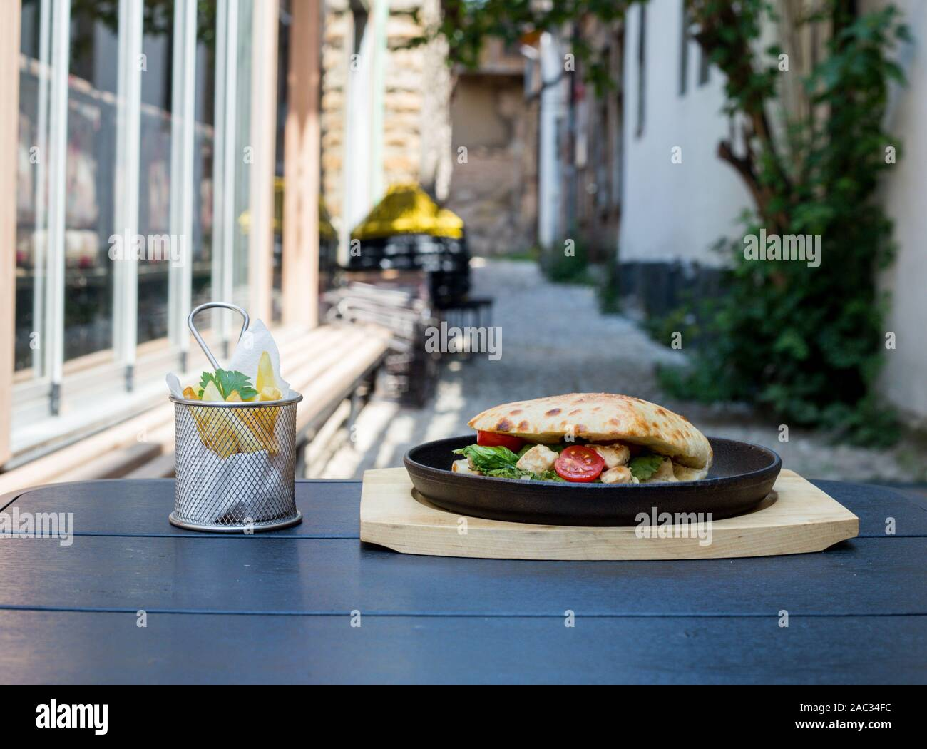 sandwich with chicken pieces, green salad and tomato, decorated with French fries and parsley leaves, black background Stock Photo