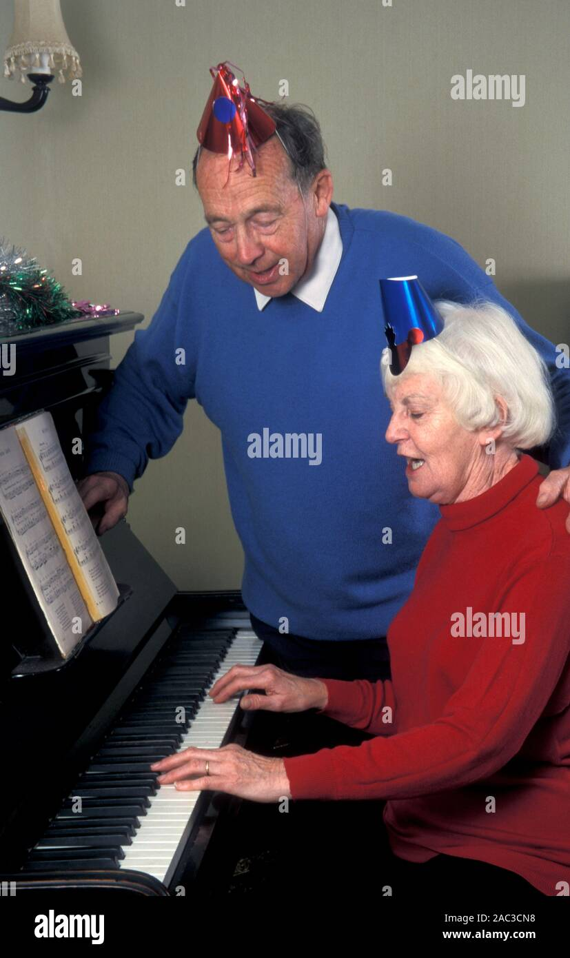 Senior couple in party hats having sing song around piano at Christmas Stock Photo