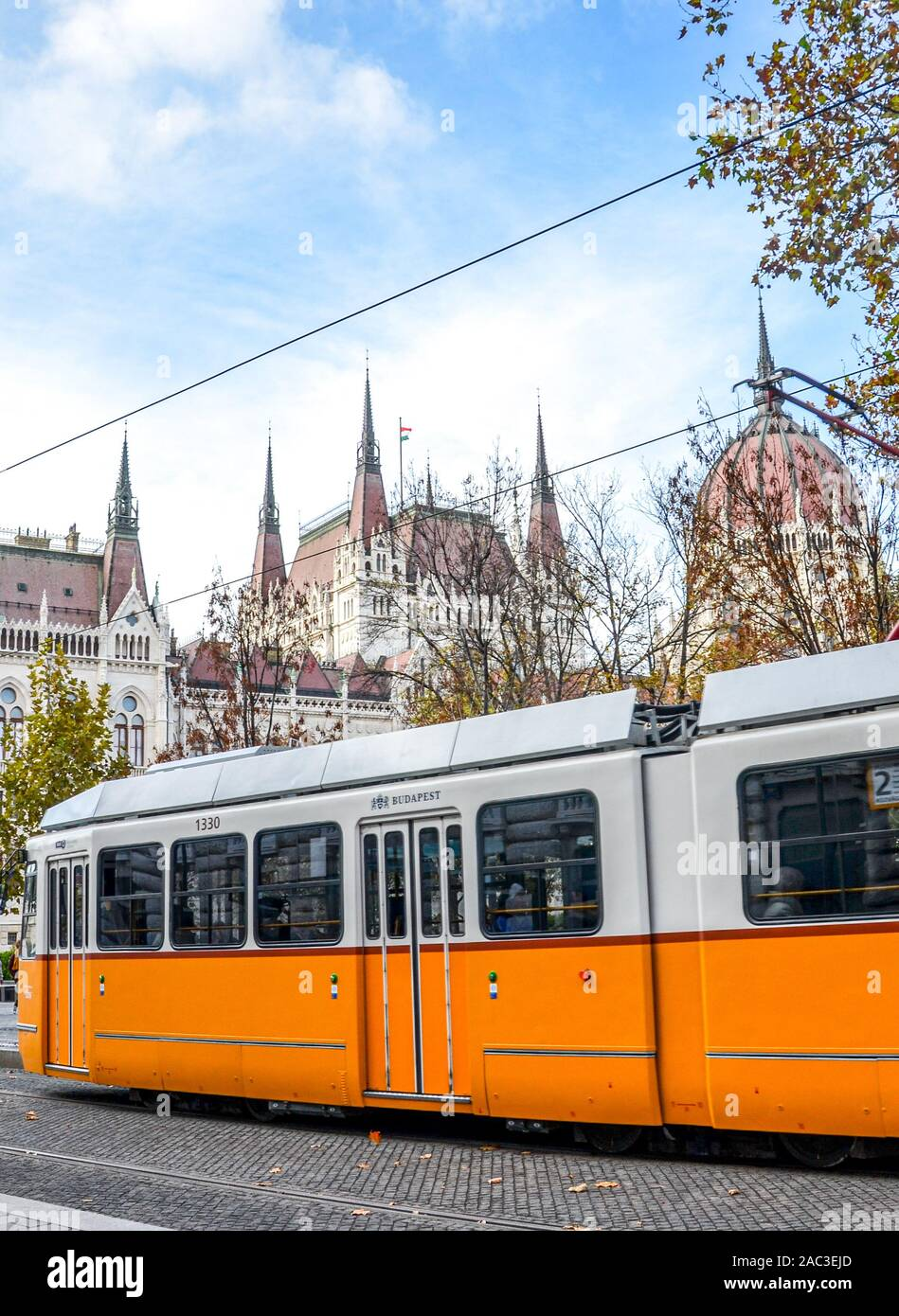 Budapest, Hungary - Nov 6, 2019: Public yellow tram riding in front of the Hungarian Parliament building. Hungarian capital city public transport. City transportation. Eastern European destinations. Stock Photo