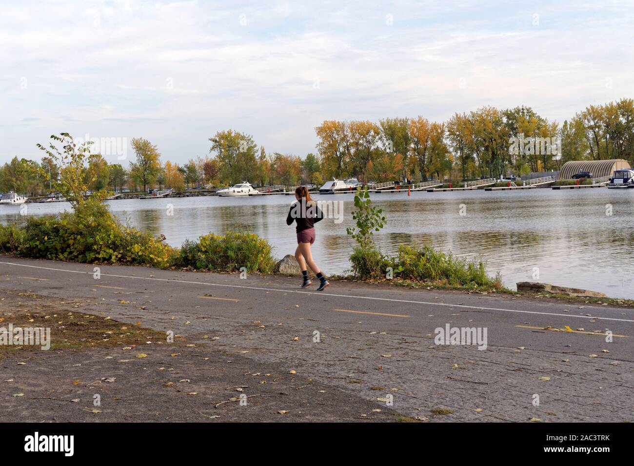 Young woman jogging beside the Lachine Canal in Lachine, Montreal, Quebec, Canada Stock Photo