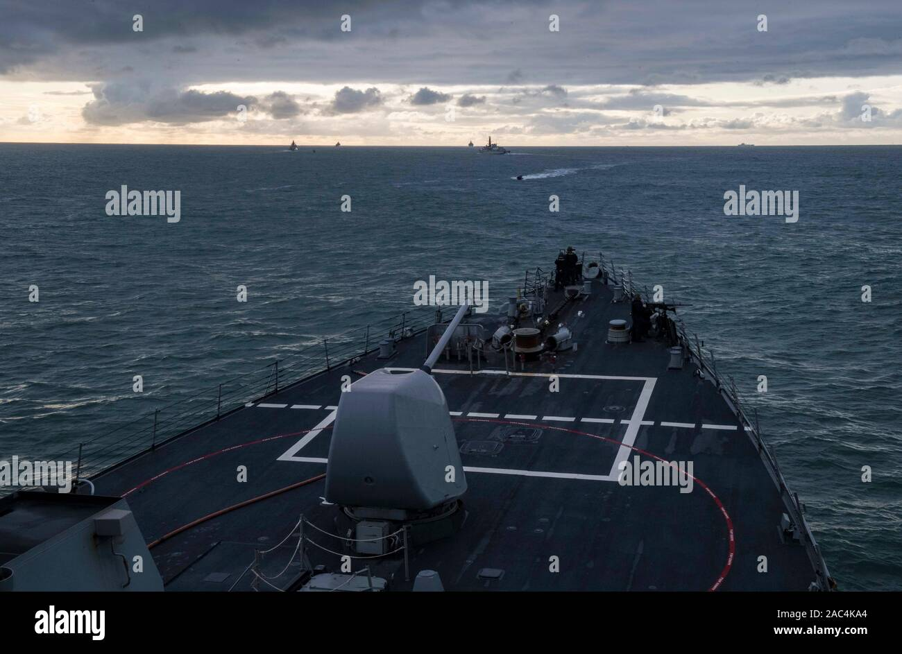 191128-N-TI693-1108    ATLANTIC OCEAN (Nov. 28, 2019) - Sailors man .50-caliber machine guns on the forecastle aboard the Arleigh Burke-class guided-missile destroyer USS Carney (DDG 64) in response to an incoming (simulated) hostile small craft as part of the small caliber arms team during the U.K.-led Flag Officer Sea Training (FOST), Nov. 28, 2019. FOST's training is designed to prepare all types of navy vessels and auxiliaries for peacetime, peace-support, and war-fighting operations. Carney, forward-deployed to Rota, Spain, is on its seventh patrol in the U.S. 6th Fleet area of operations Stock Photo