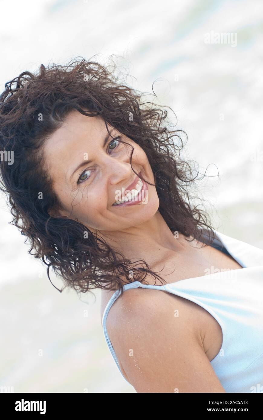 Portrait taken at Kailua beach of beautiful curly haired woman at age 50 wearing soft blue dress Stock Photo