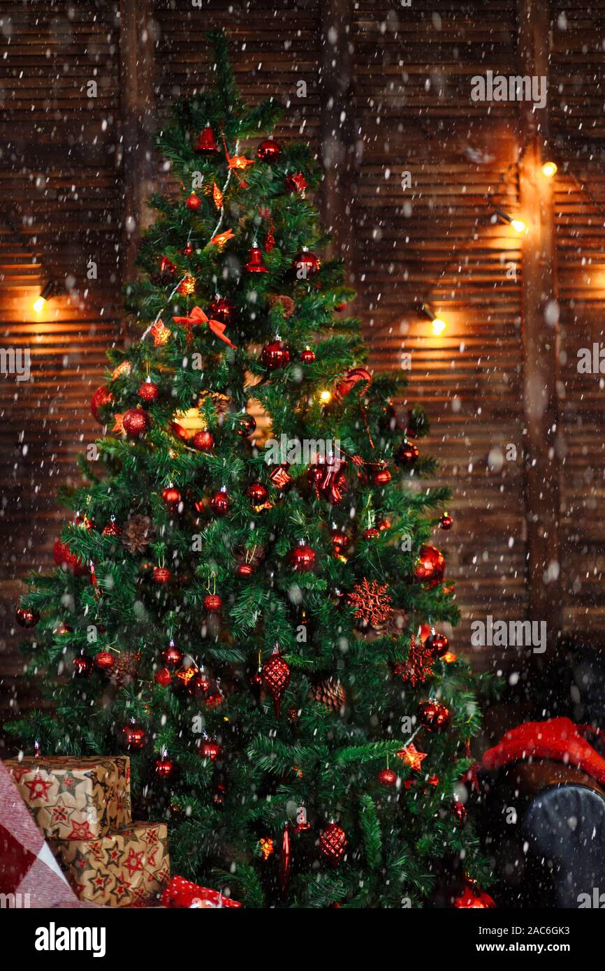 Green Christmas Tree Decorated With Red Toys Ornaments Pine Cones Beads Garlands Box Sofa Wooden Wall Floor In The Dark Stock Photo Alamy