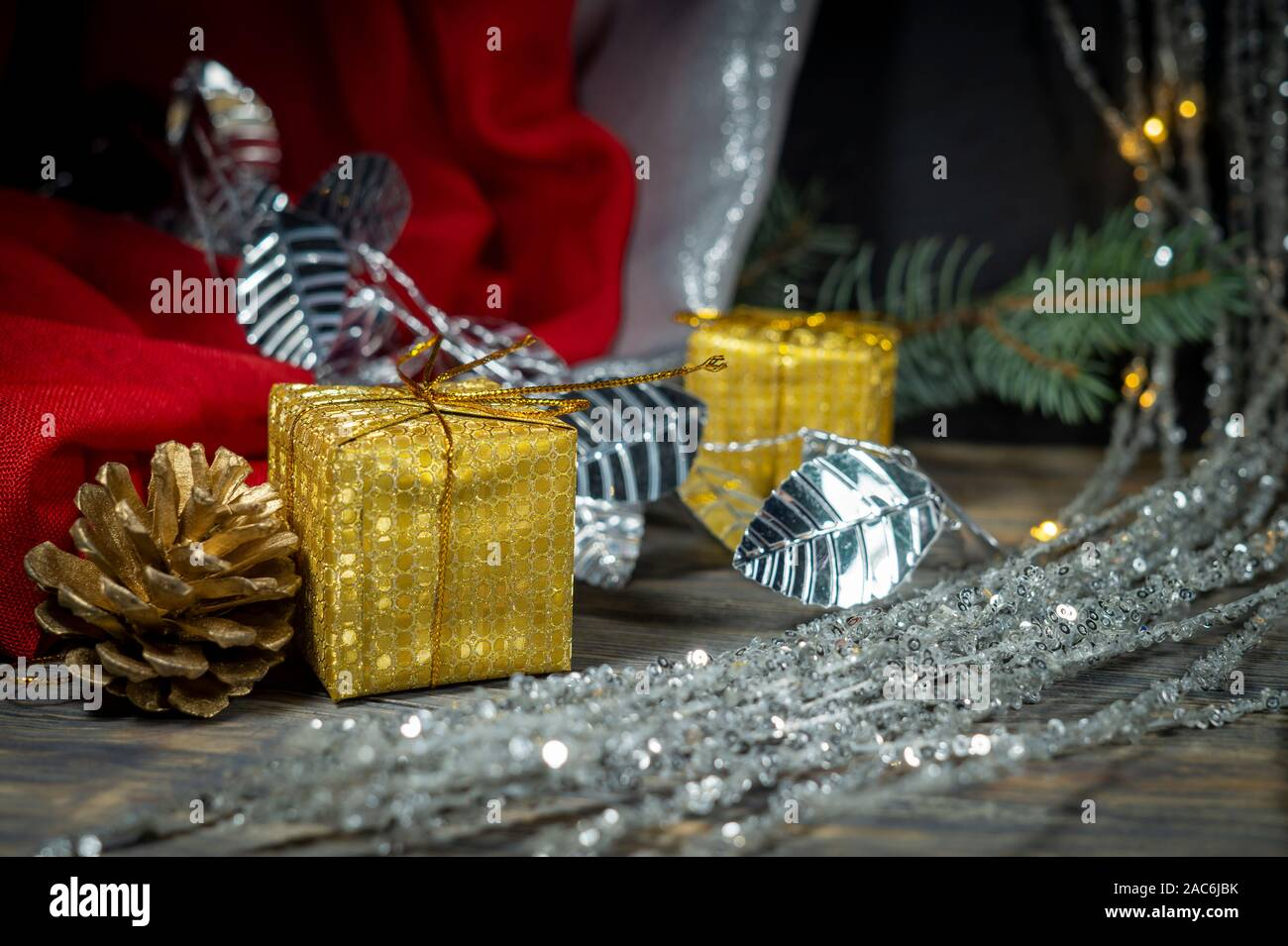 festive christmas background with golden t and cone with a pine branch colorful red drape and assorted decorations 2AC6JBK