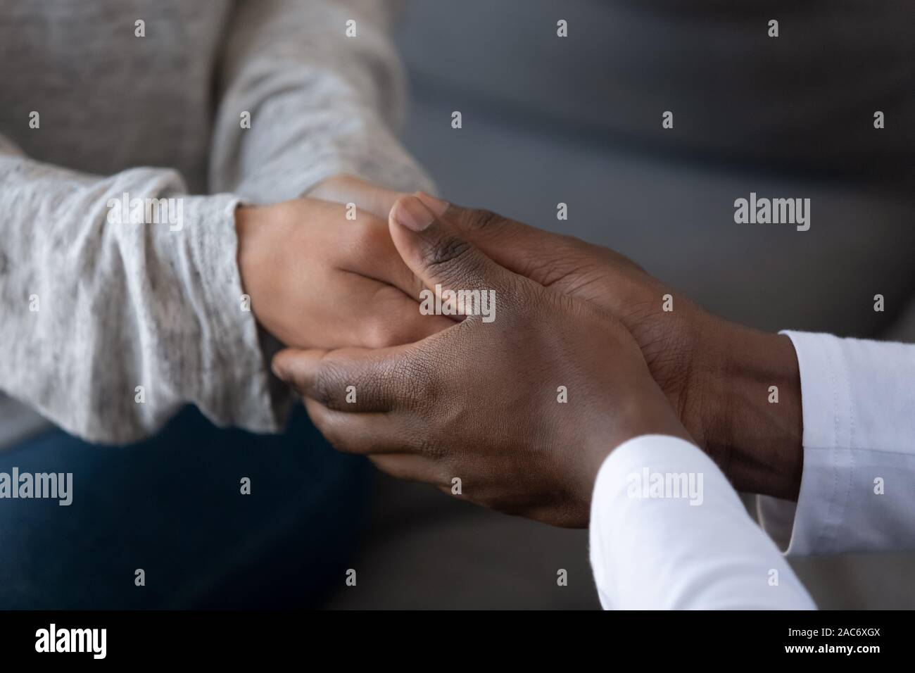 Young african american guy holding hands of woman, giving support. Stock Photo
