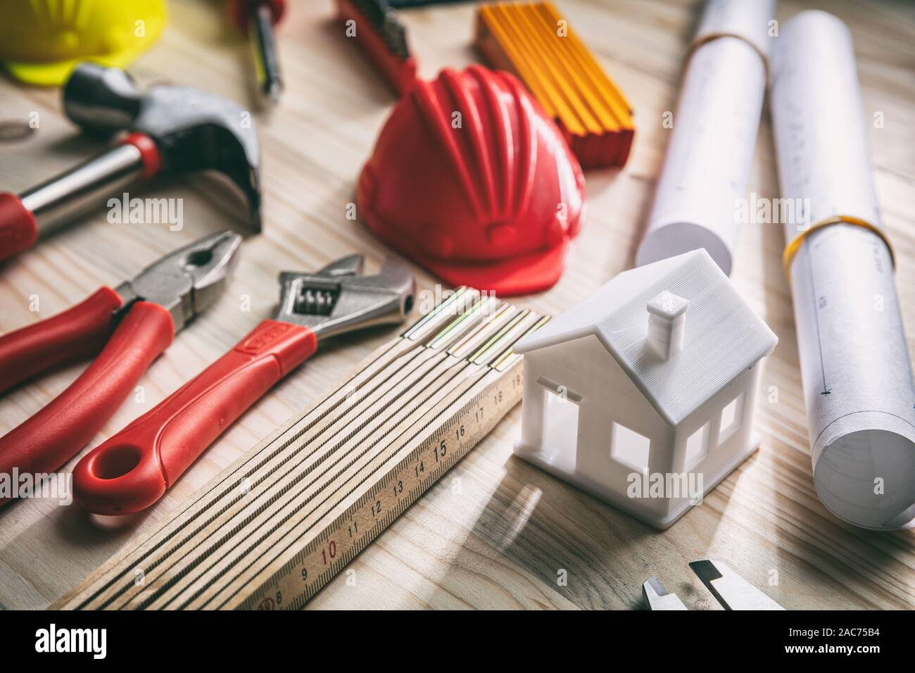 Construction, house renovation concept. Hand tools, hard hats and project blueprints on wood, close up view Stock Photo