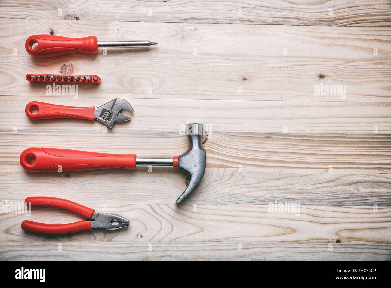 Hand tools set red color on wood, copy space, top view. DIY, repair, maintenance concept Stock Photo