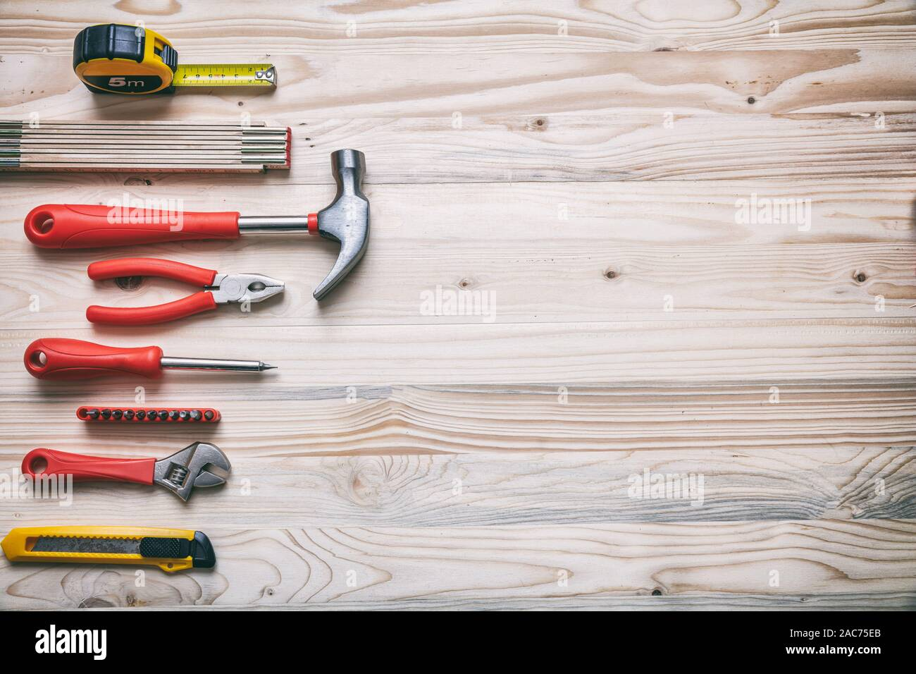 DIY, repair, service concept. Hand tools set red and yellow color on wood, copy space, top view. Stock Photo