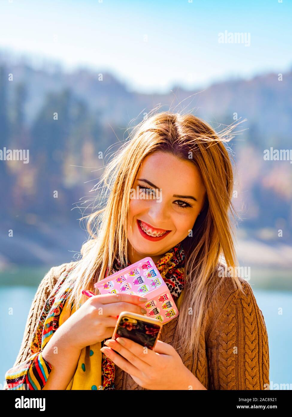 Young woman busy with small note paper notebook and smartphone in hands smiling with teeth braces giggling giggle Stock Photo