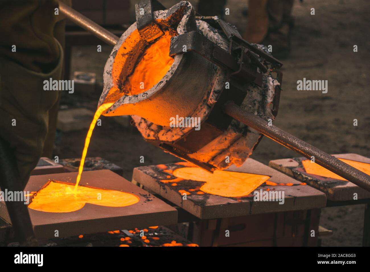 iron casting into a heart mold in an outside workshop Stock Photo