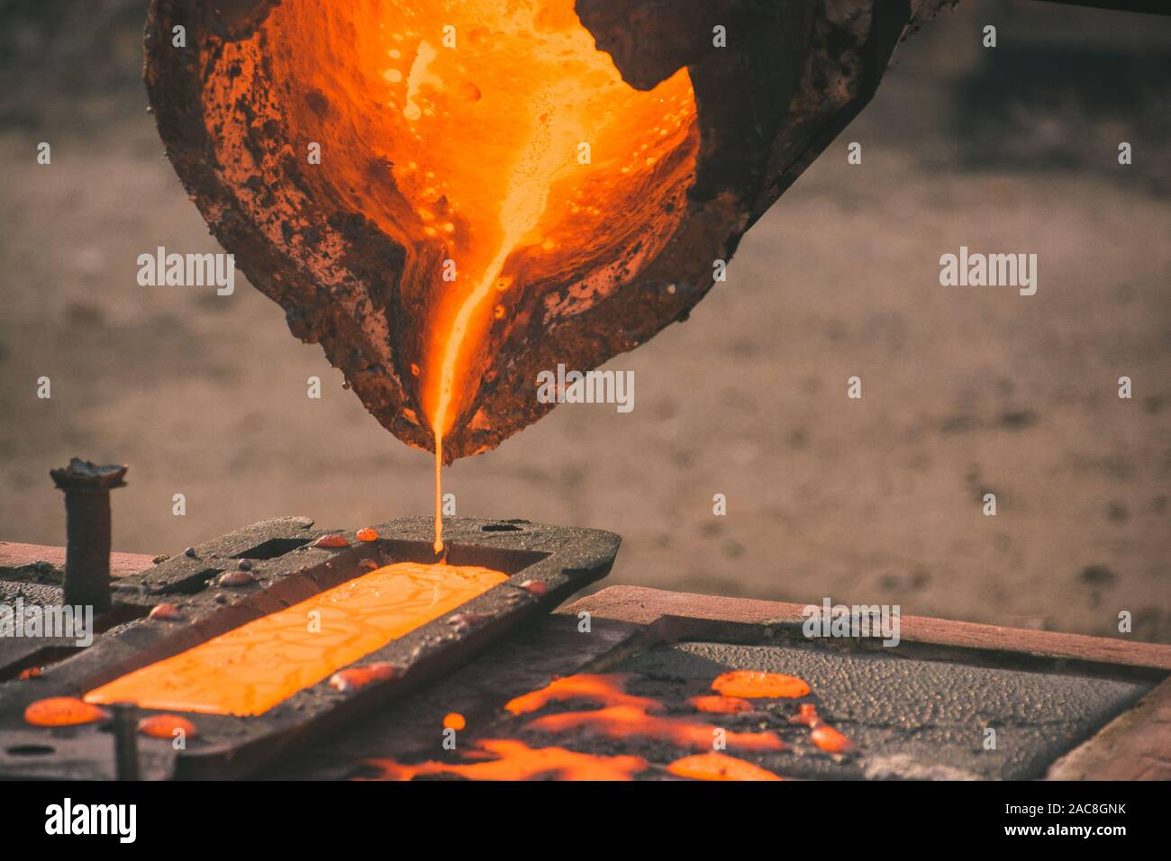 iron casting into a mold in an outside workshop Stock Photo