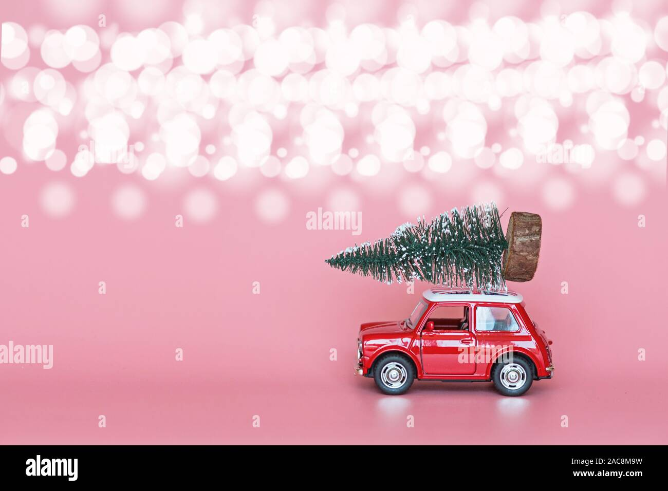 Red toy car with a christmas tree on the roof on pink paper background. Winter delivery, xmas, happy new year 2020 celebration concept. greeting card Stock Photo