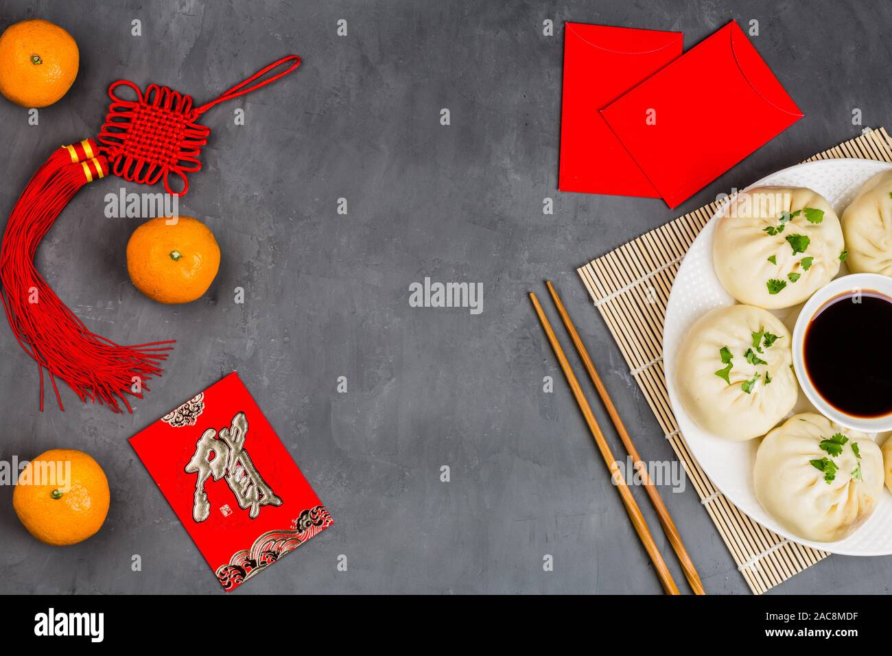 Chinese New Year decoration with dumplings, tangerines, soy sauce, chopsticks, red envelopes on gray concrete background. Happy Chinese new year 2020 Stock Photo