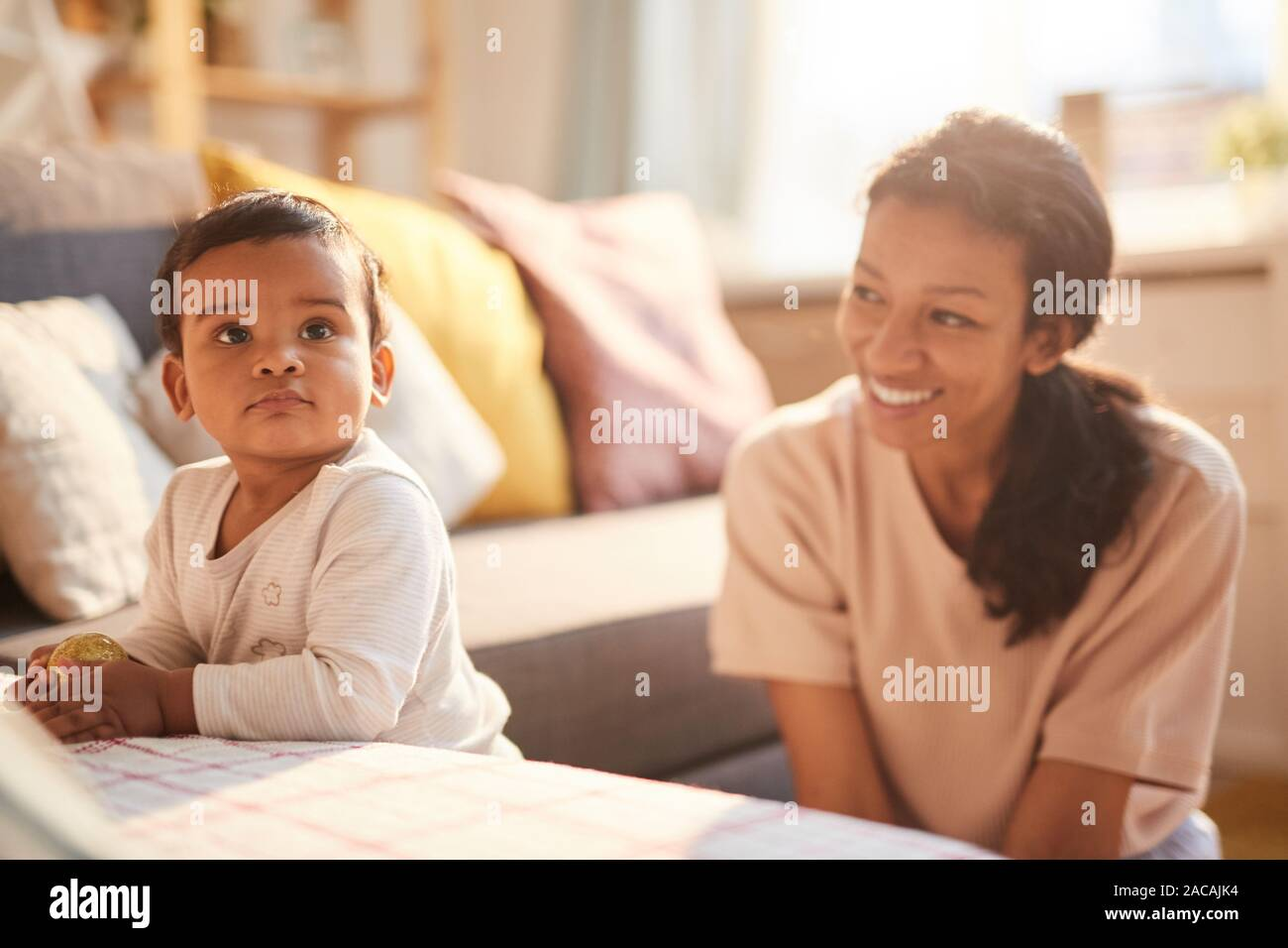 Smiling young mother sitting and playing with her little child on the sofa in the room Stock Photo