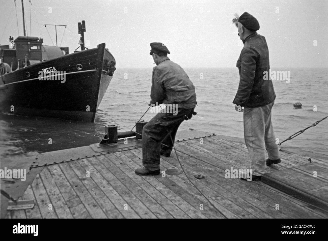 Schiffsarbeiter setzen Bojen, Emden, Niedersachsen, Deutschland, 1950. Ship workers put buoys, Emden, Lower Saxony, Germany, 1950. Stock Photo