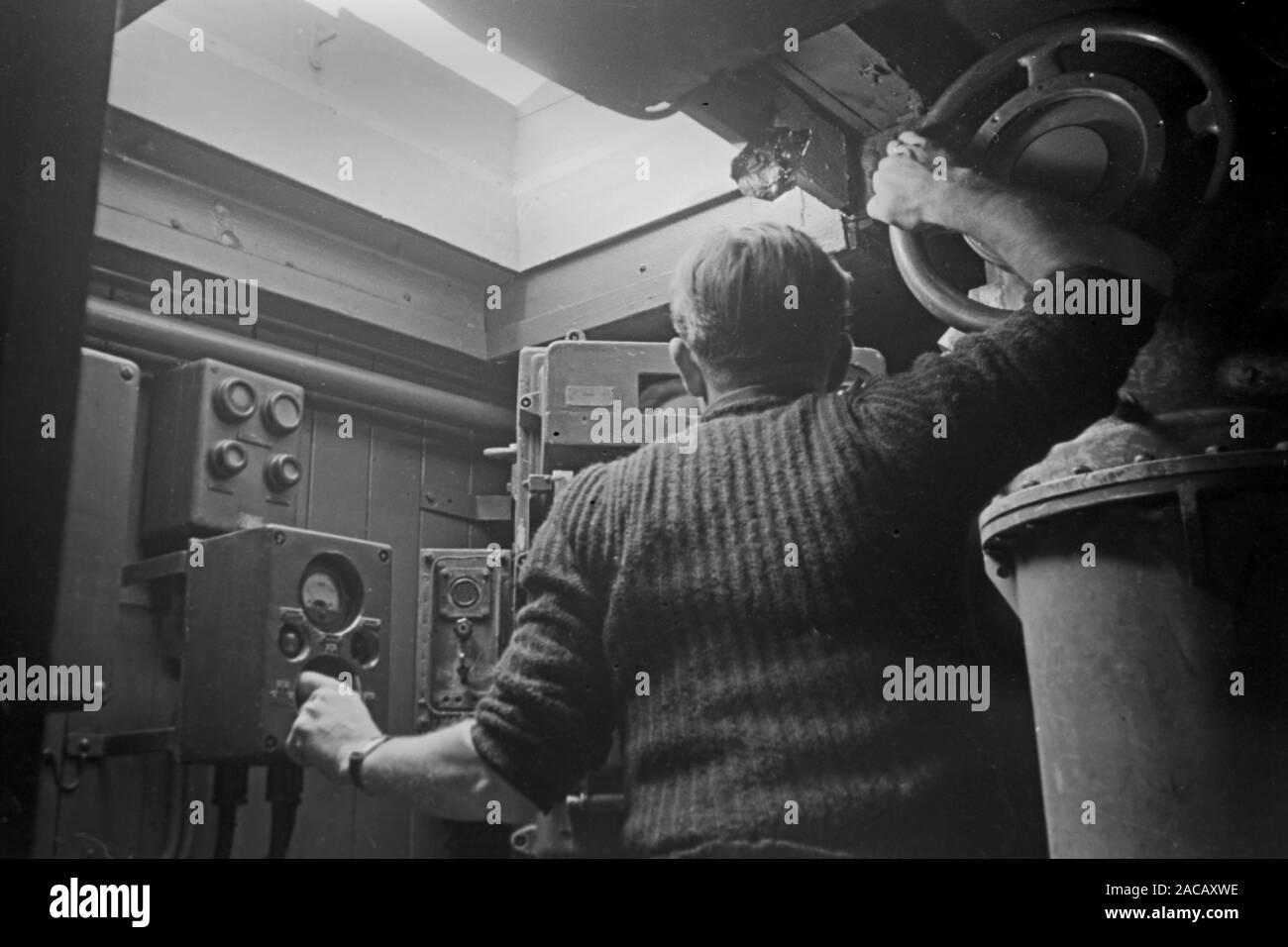 Schiffsarbeiter prüft Luftzufuhr für Taucher, Emden, Niedersachsen, Deutschland, 1950. Ship worker checks air supply for divers, Emden, Lower Saxony, Germany, 1950. Stock Photo