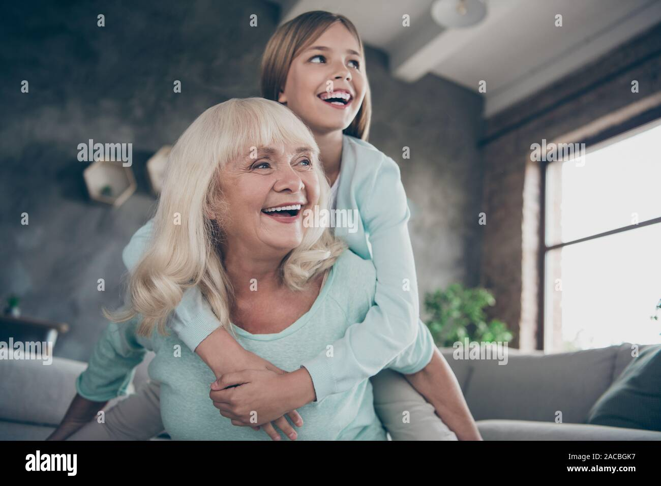Low angle view photo of two best friends people cute aged granny small grandchild girl hug piggyback playing funny game spend weekend together house Stock Photo