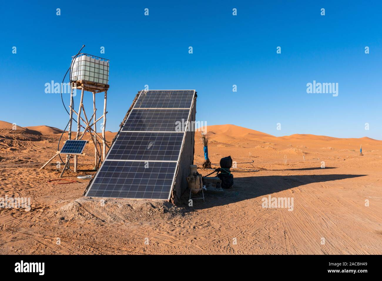 Solar energy panel and water tank in the desert. Sun as ...