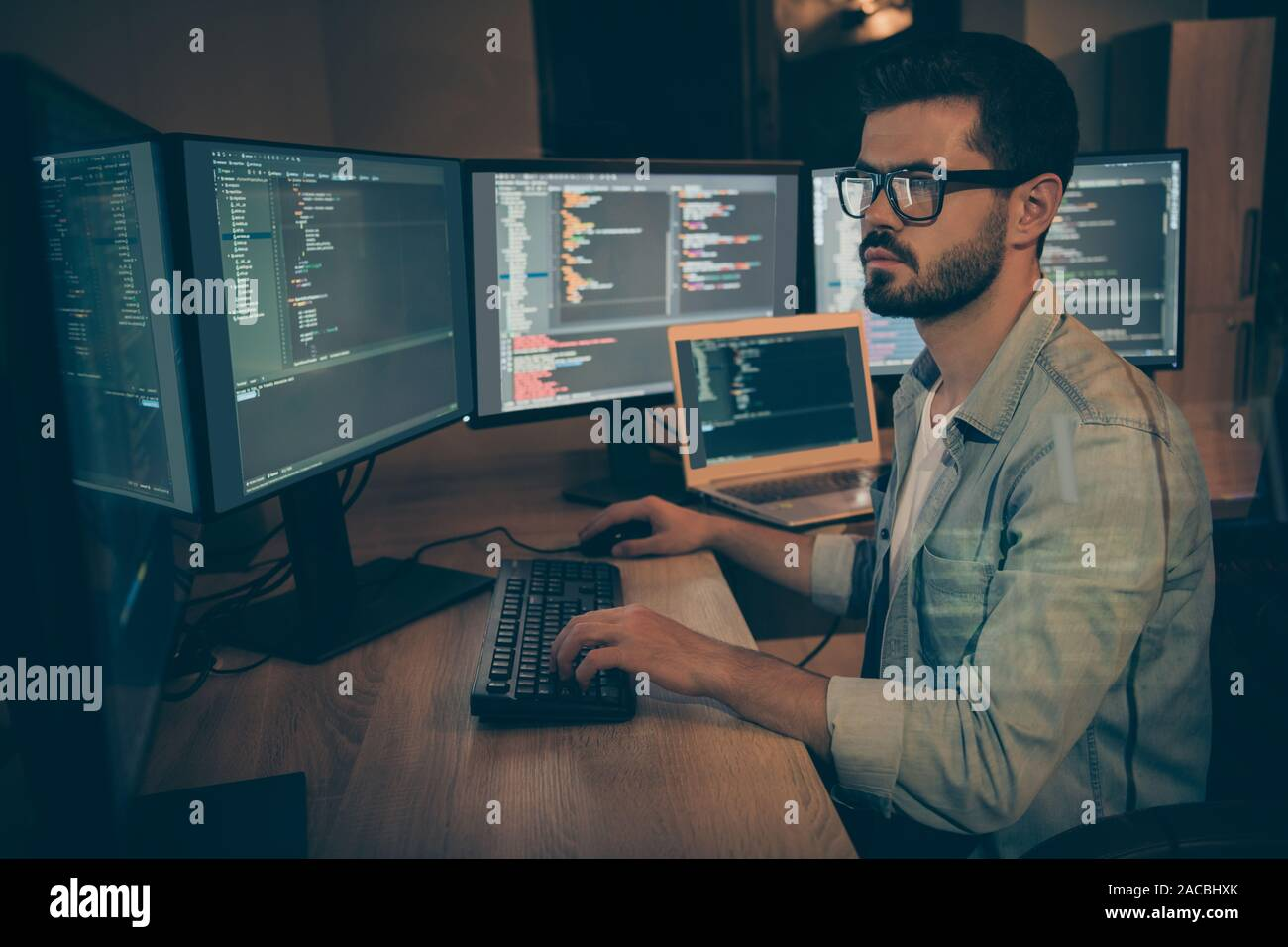Photo of serious administrator responsible for cyber security of large corporation searching for safety gaps debugging existant operating system to Stock Photo