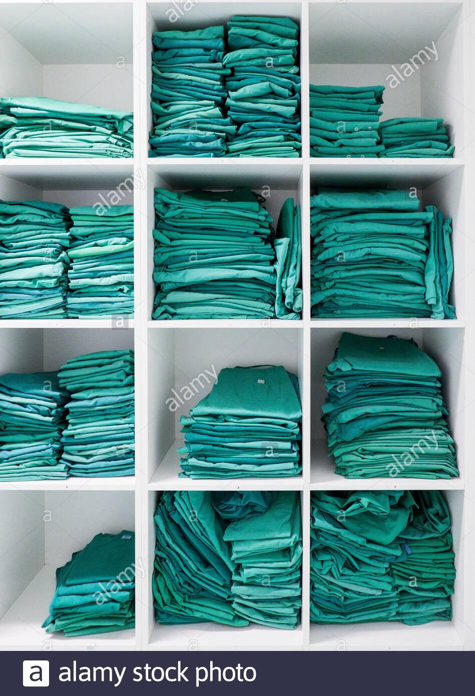 Grüne OP Kleidung in einem Regal in einem Krankenhaus Stock Photo