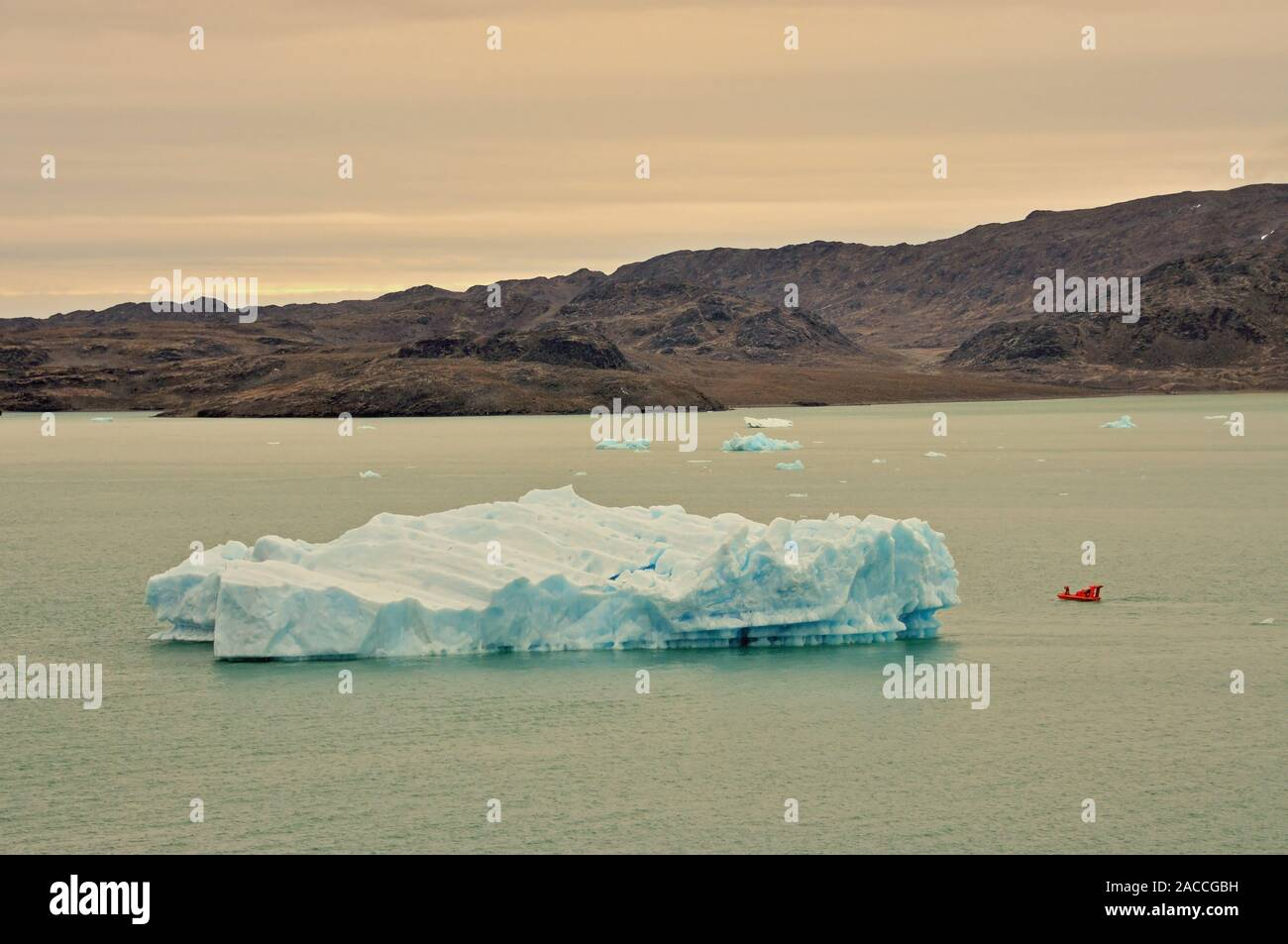 A small boat beside an iceberg in Krossfjorden, off the west coast of Spitsbergen, in evening light. Stock Photo