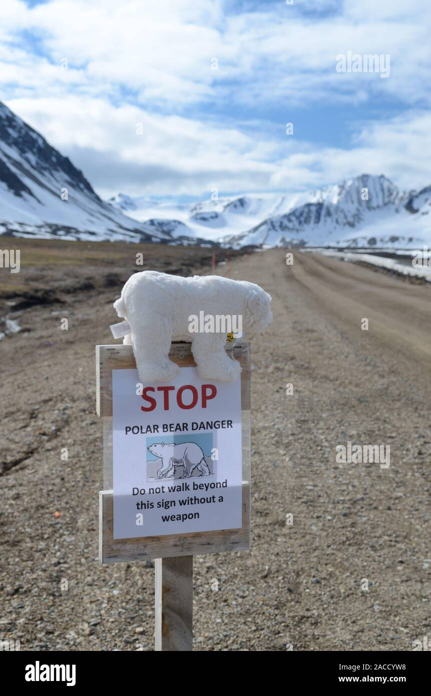 Sign at Ny Alesund warning about polar bears, complete with a toy bear. Stock Photo