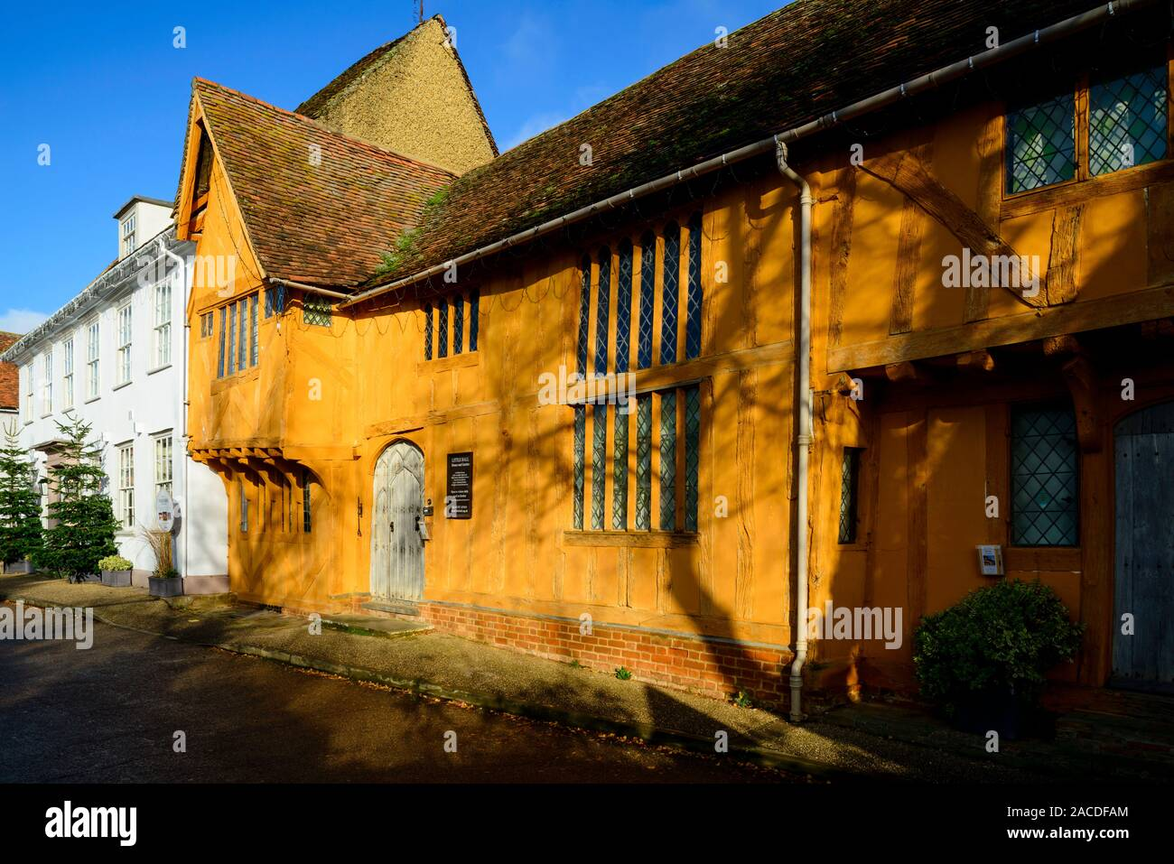 The orange painted Little Hall, which is a late 14th Century timber-famed house in the Market Place, Lavenham, Suffolk, England, UK Stock Photo
