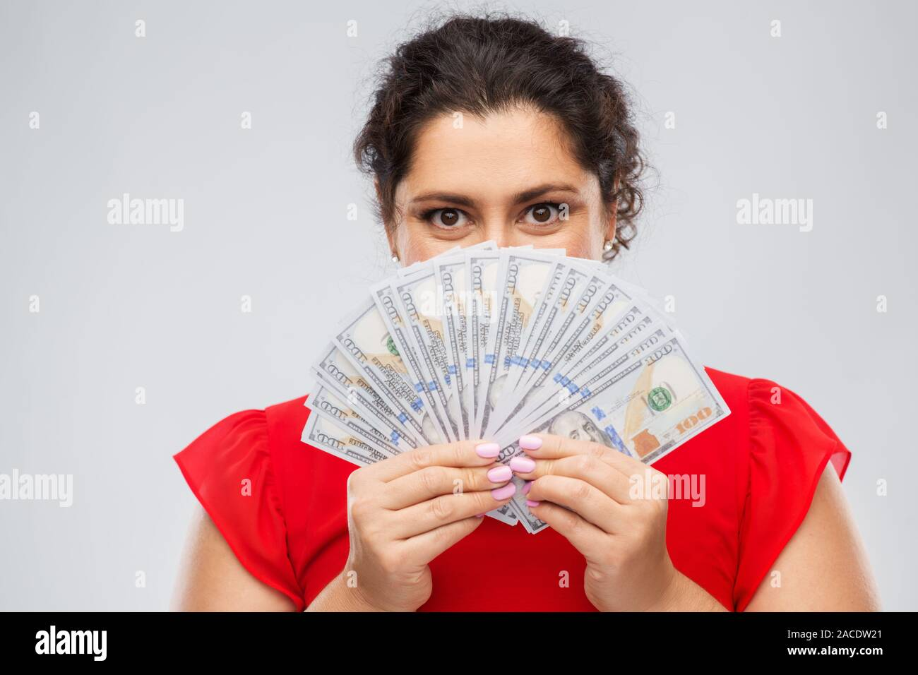 woman hiding her face behind money banknotes Stock Photo