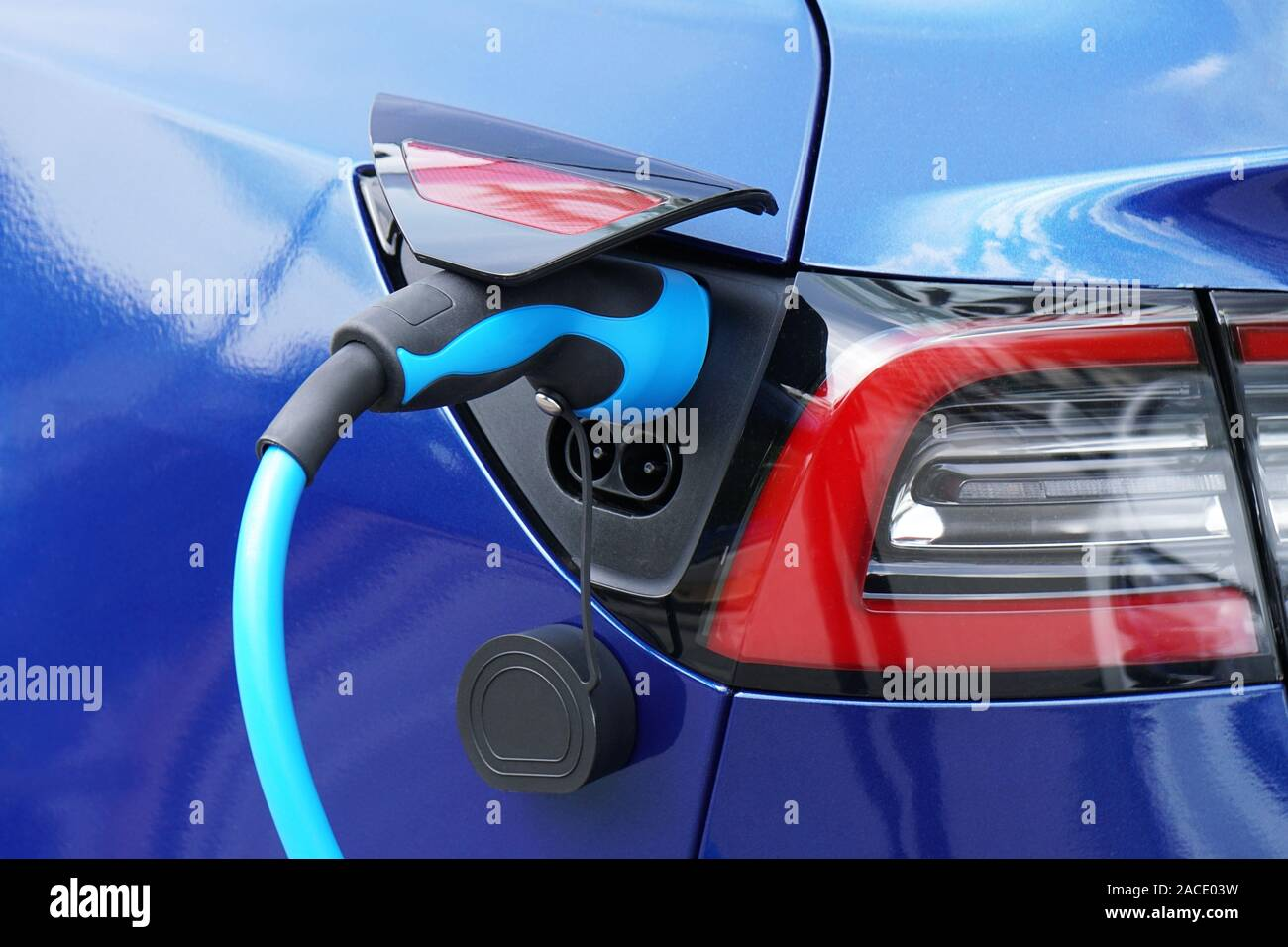 EV or Electric car at charging station with plug-in power supply cable - e-mobility concept Stock Photo