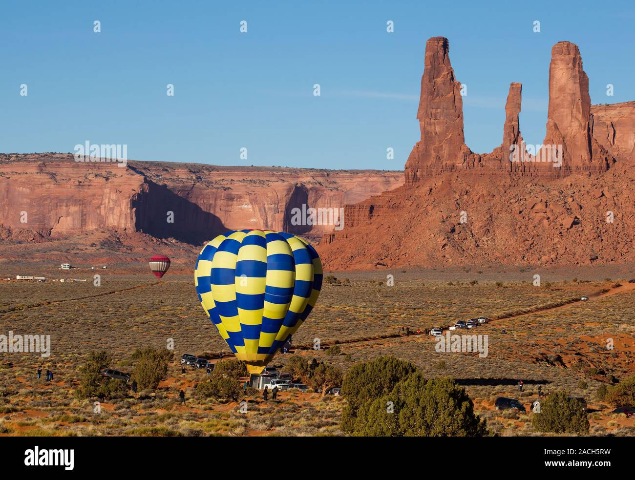 A team prepares for launch in the Monument Valley Navajo Tribal Park in Arizona.  In the background is the rock formation called the Three Sisters at Stock Photo
