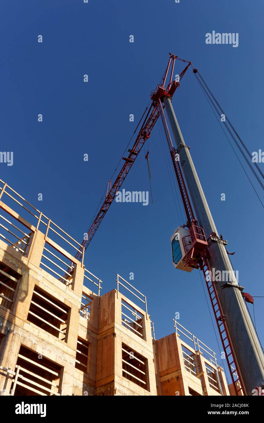 Telescopic construction crane and wood frame residential building site, Vancouver, BC, Canada Stock Photo