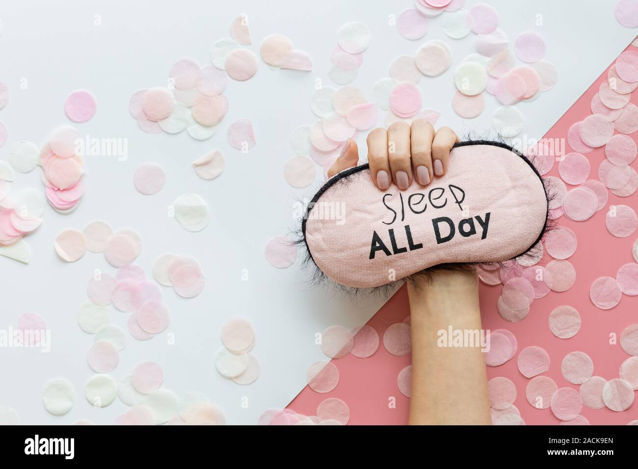 Healthy sleep concept. Female hand holding Sleeping mask on pink background with confetti. Flat lay, top view copy space, mock up, overhead, template Stock Photo