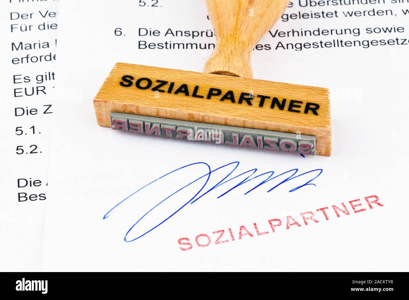 Wooden stamp on document: Social partners Stock Photo