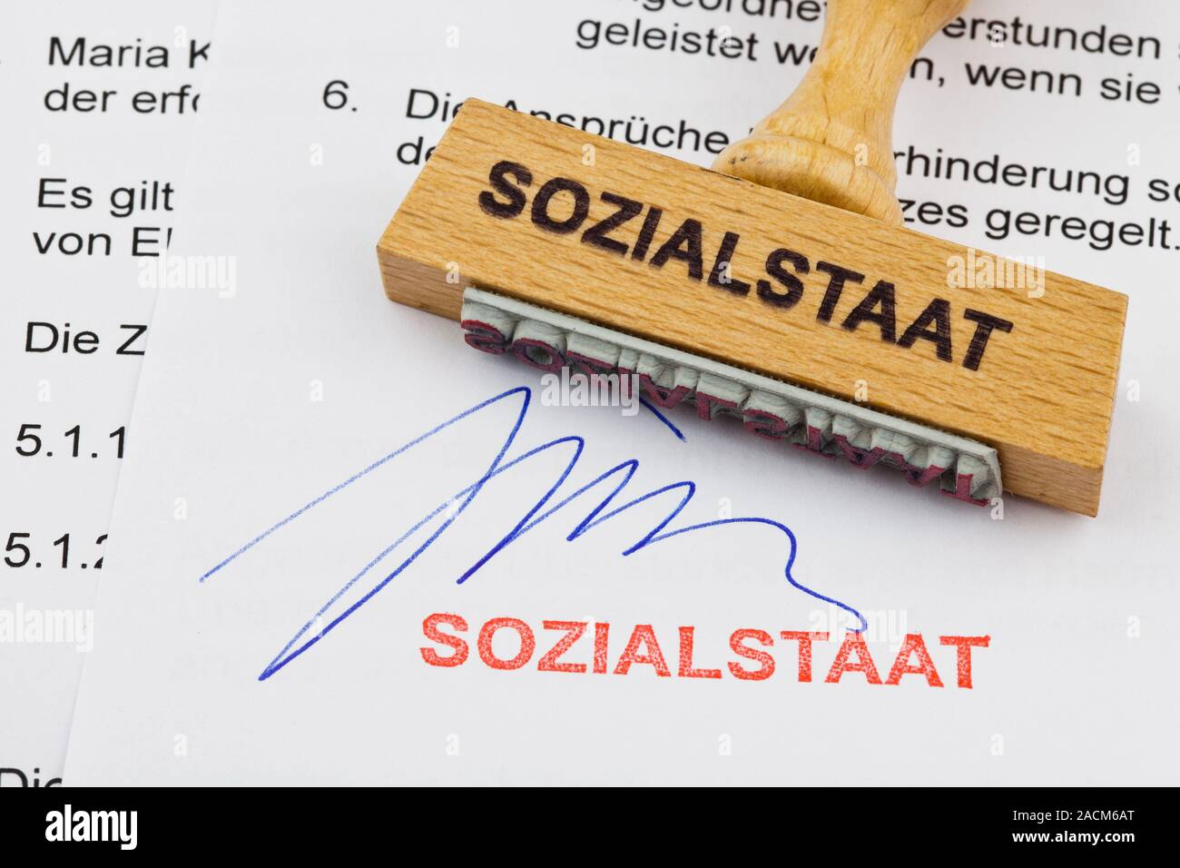 Wood stamp on document: welfare state Stock Photo