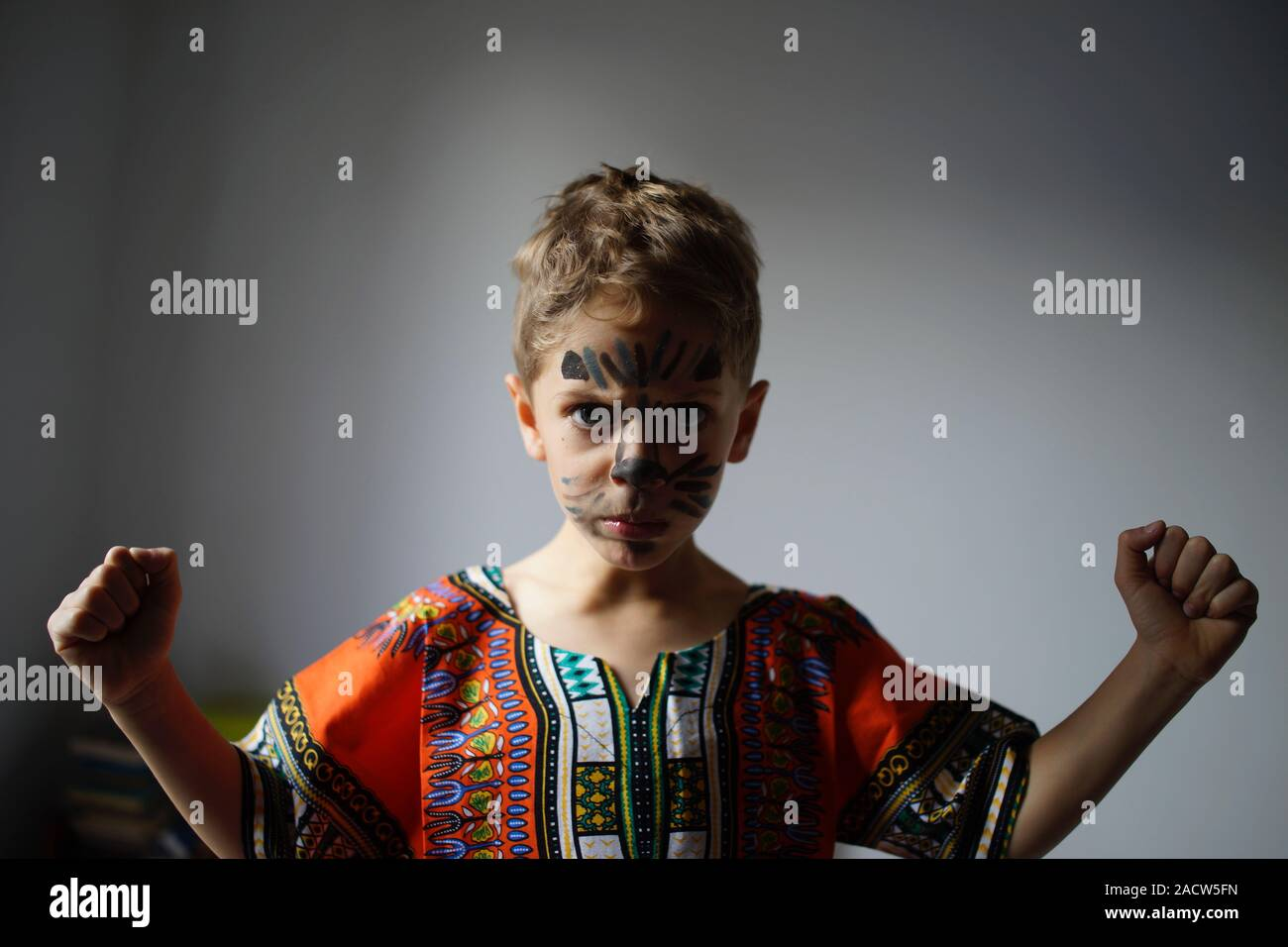 Boy with painted face and raised fists, raised wearing traditional African Dashiki shirt Stock Photo