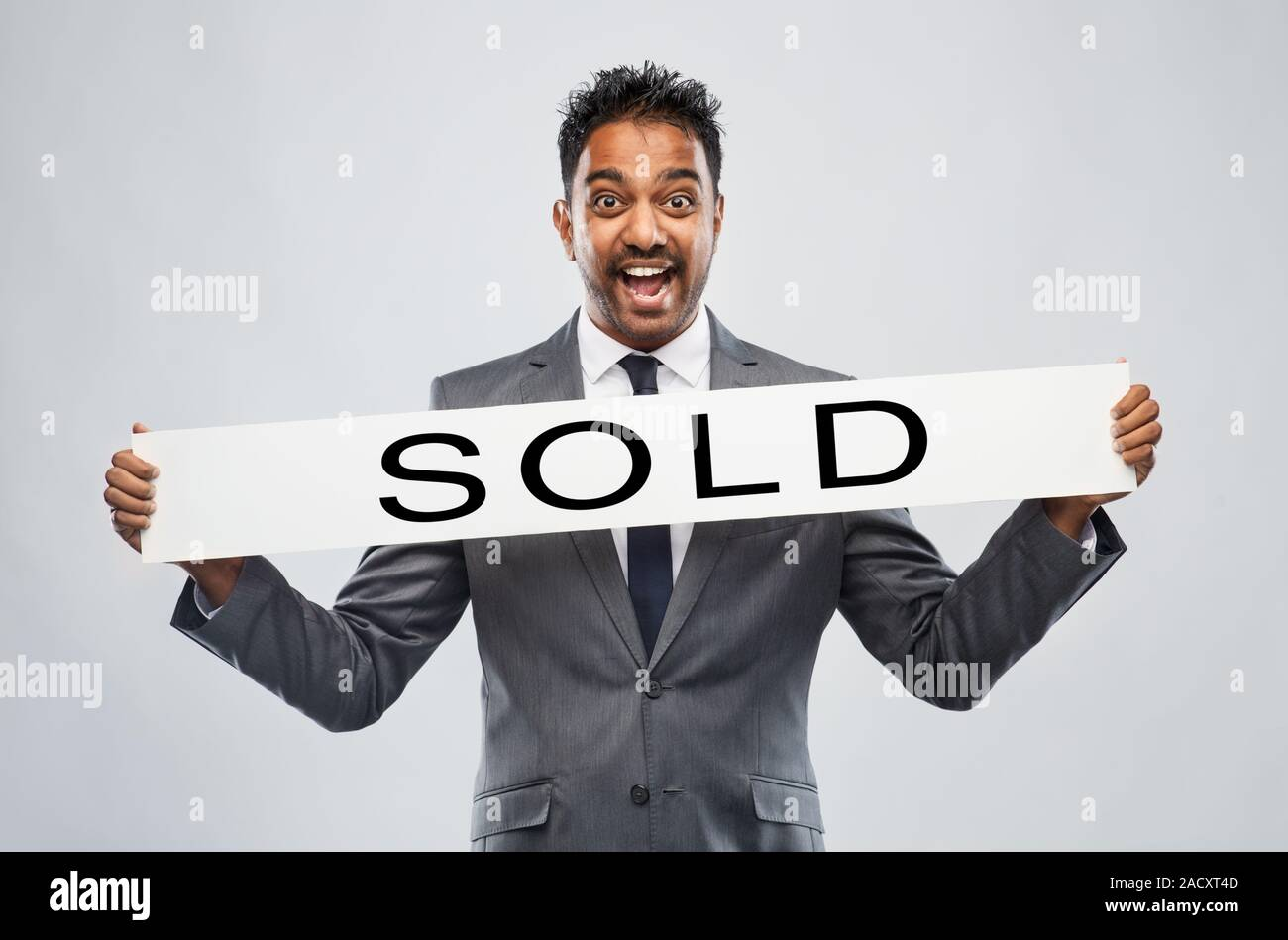 Real Estate Business Realty Sale And Success Concept Happy Indian Male Realtor With Sold Banner Over Grey Background Stock Photo Alamy