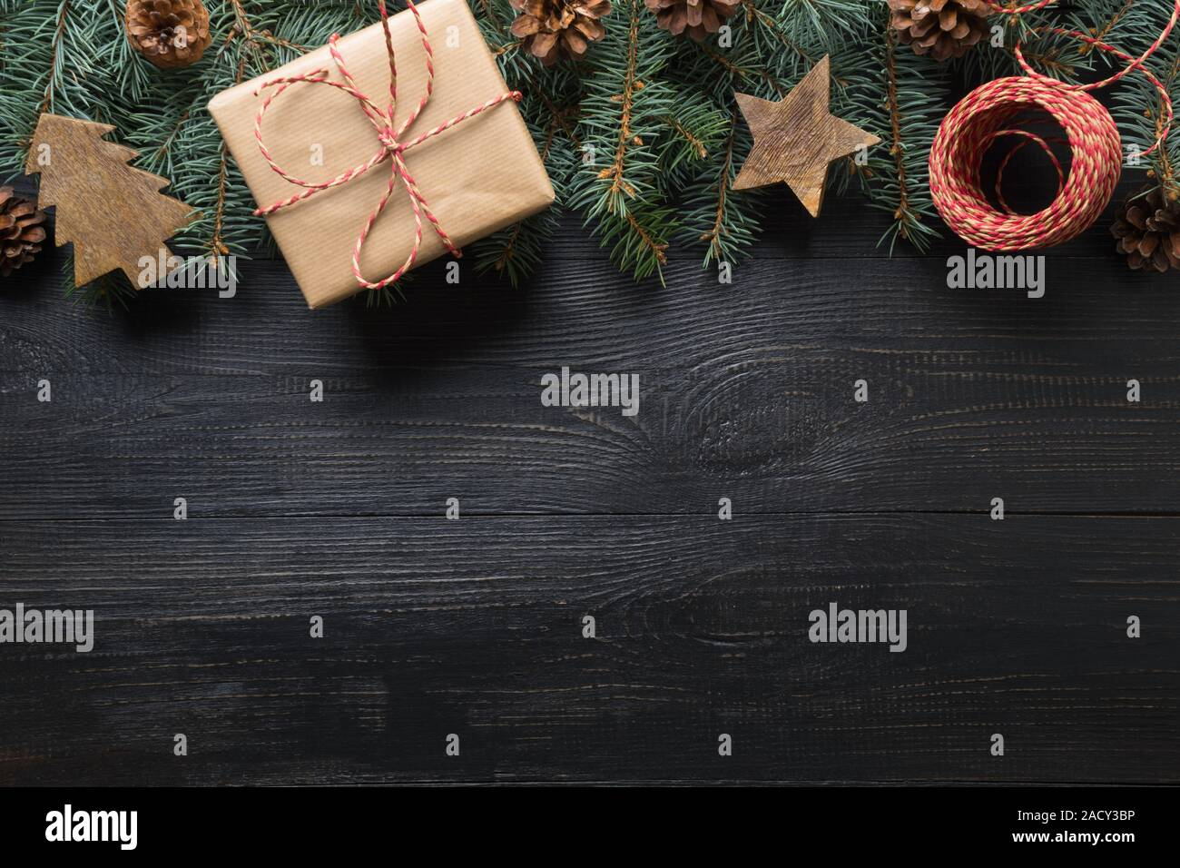 Christmas frame of fir branches, gift and wooden toys on dark wooden board. Top view. Space for text. Zero Waste Holiday. Eco friendly. Stock Photo
